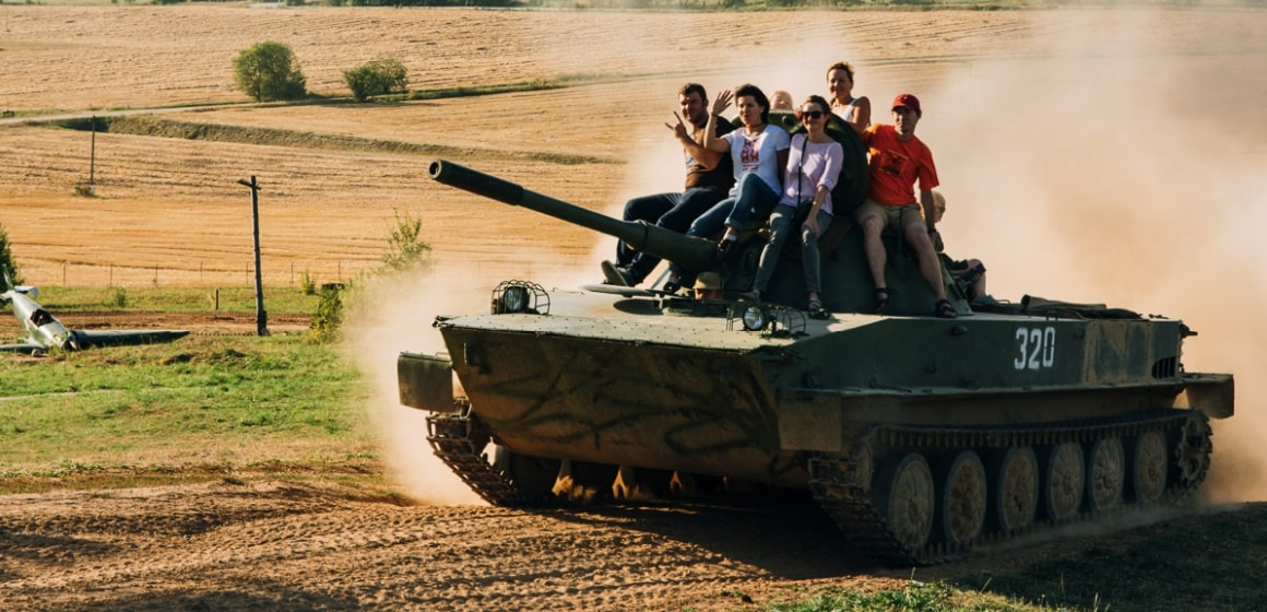 People ride a tank during Stalin Line Tour